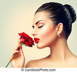 Fashion brunette model girl face portrait with red rose in her hand