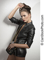 fashion brunette with leather clothes and hand on the head