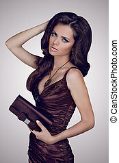 Fashion brunette woman in elegant dress with bag. Jewelry and Beauty. Fashion photo