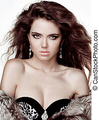 Fashion brunette woman in fur coat with evening make-up. Jewelry and Beauty.