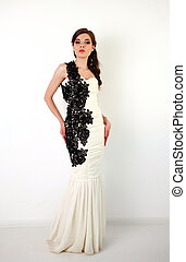 Fashion brunette woman in long dress in studio on white background