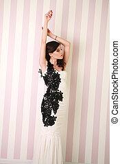 Fashion brunette woman in long dress in studio