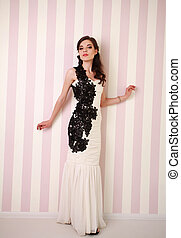 Fashion brunette woman in long dress in studio