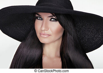 Fashion brunette woman model posing in black hat isolated on white background