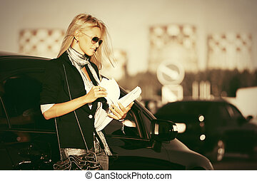 Fashion business woman in sunglasses next to her car