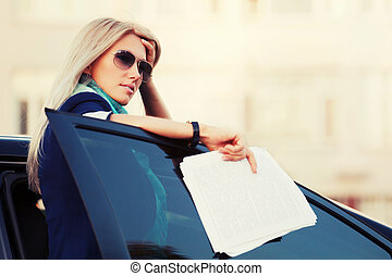 Fashion business woman in sunglasses standing her car