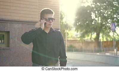 Fashion businessman speaking on the phone and smoking e-cigarette on street