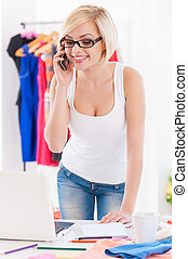 Fashion consultant at work. Cheerful young woman talking on the mobile phone and looking at laptop