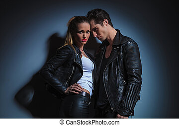fashion couple in leather is posing in studio background