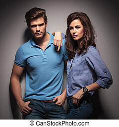 Fashion couple leaning on a grey wal