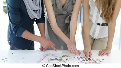 Fashion design team looking at costume jewelry and model...
