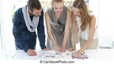 Fashion design team looking at costume jewelry in their...