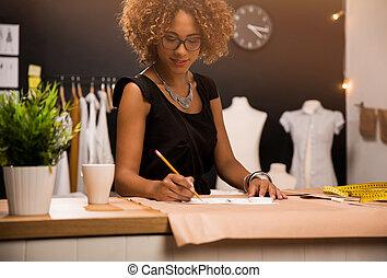 Fashion designer - A young fashion designer working on her ...