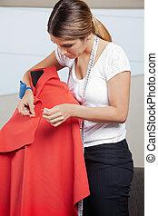 Fashion Designer Adjusting Pins On Fabric