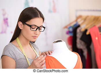 Fashion designer at work. Beautiful young woman in glasses working in fashion design studio