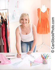 Fashion designer at work. Cheerful young woman working at fashion design studio