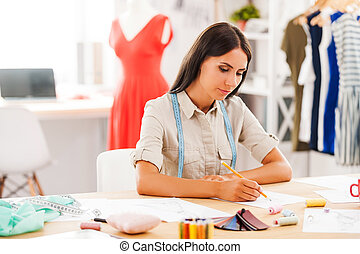 Fashion designer at work. Serious young woman drawing while sitting at her working place in fashion workshop