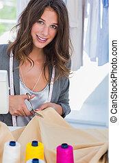 Fashion designer cutting textile next to a sewing machine