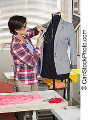 Fashion Designer Fixing Suit On Mannequin