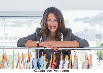 Fashion designer leaning on clothes