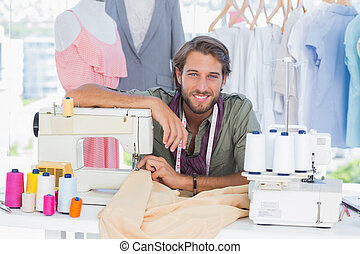 Fashion designer leaning on sewing machine
