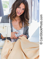 Fashion designer looking at camera and cutting textile