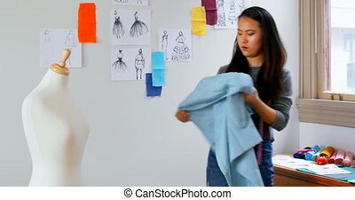 Fashion designer looking at sketch and measuring the fabric...