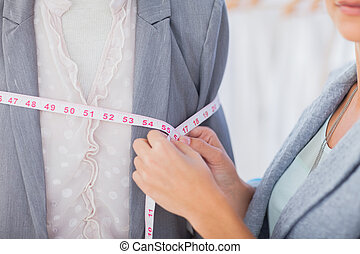 Fashion designer measuring blazer with measuring tape