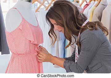 Fashion designer measuring dress on a mannequin