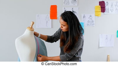 Fashion designer measuring the fabric on dressmakers model...