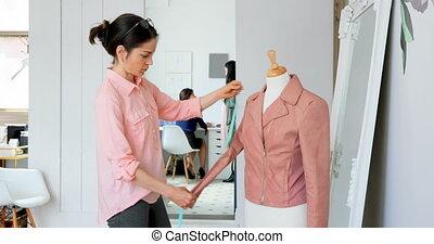 Fashion designer measuring the jacket on dressmakers model...