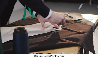 Fashion designer or tailor working with fabric at the studio full of tailoring tools. Pattern, scissors, tape measure, and a sewing machine. Workplace of seamstress. Tailor is drawing sketch lines on material using pattern