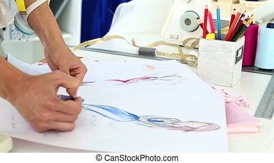 Fashion designer sketching a blue dress design in her studio