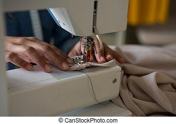 Fashion designer stitching cloth in sewing machine
