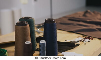 Fashion designer studio. Atelier. On the table in fashion atelier there are coils of thread, scissors, meter, tissue samples and locks