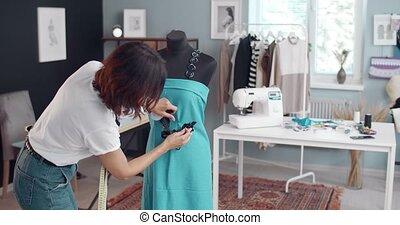 Fashion designer tailoring blue dress at atelier - Fashion ...
