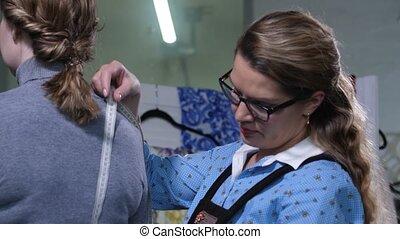 Fashion designer taking measurements of customer - Close-up...