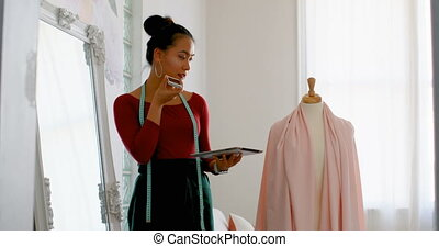 Fashion designer talking on the phone while working on dress...