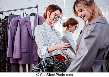 Fashion designer talking to model in new trench coat before fashion show