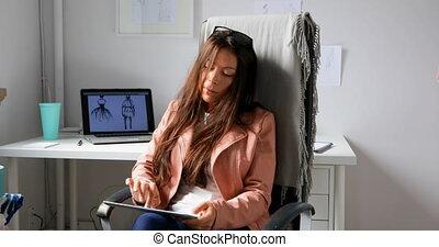 Fashion designer using digital tablet in the design studio...