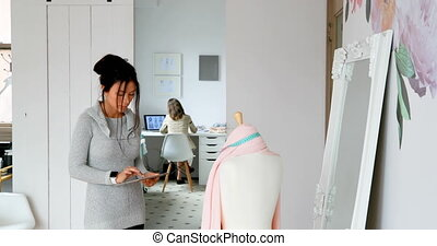Fashion designer using tablet and examining the fabric on...