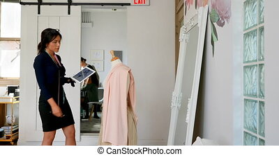 Fashion designer using tablet while working on a fabric on...