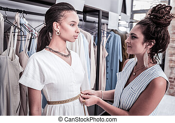 Fashion designer wearing stylish earrings talking to her model before fashion show
