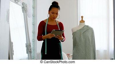 Fashion designer with digital tablet working on dressmakers...