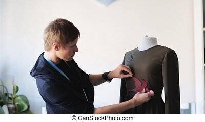 fashion designer with dummy making dress at studio - people,...