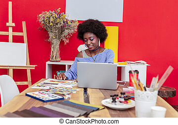 Fashion designer working hard in her office before fashion show