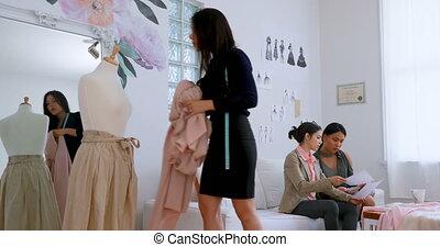 Fashion designer working on dressmakers model while other...
