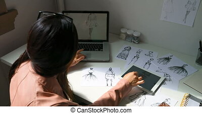 Fashion designer working on sketches of dress at design...