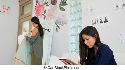 Fashion designer working on tablet and a fabric on dress...