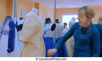 Fashion designer working with new model tailoring dress on mannequin